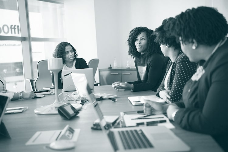 women in a meeting duotone - customer churn management